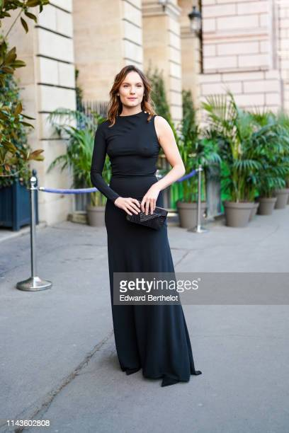 Ana Girardot wears a black one -sleeve long flowing dress, a black clutch, on April 12, 2019 in Paris, France.