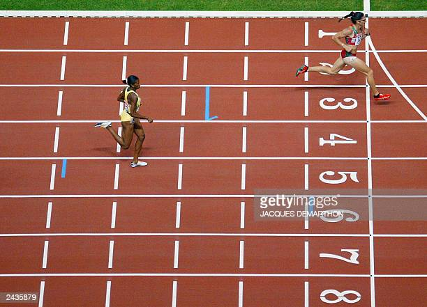 Ana Guevara of Mexico finishes first to win gold in the women's 400m final ahead of Lorraine Fenton of Jamaica in second place 27 August 2003 during...