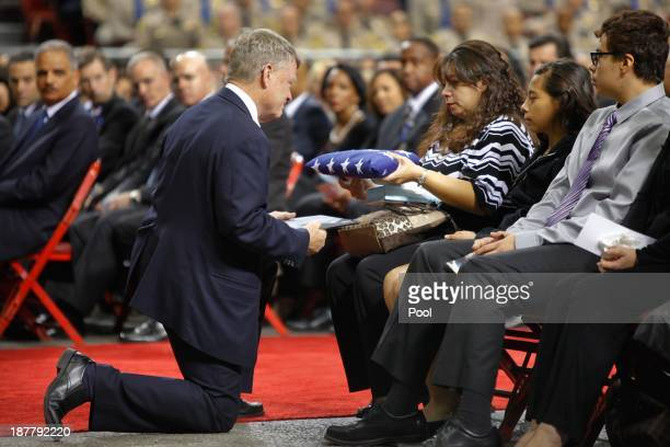 Ana Hernandez flanked by her children Stephanie and Luis accepts the flag from acting Department of Homeland Security Chief Rand Beers during a...