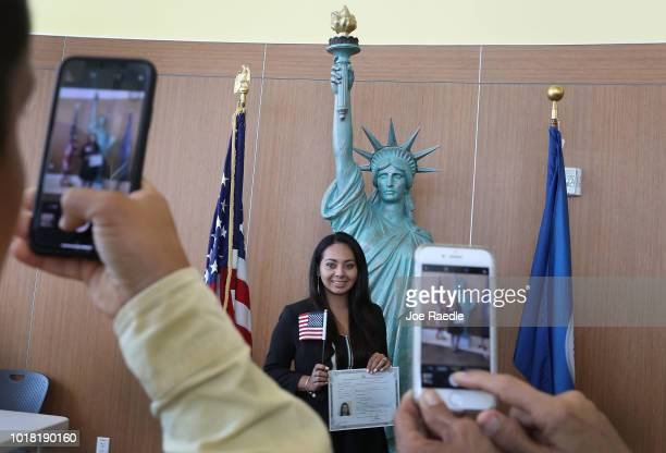 Ana Herrera poses for a family picture in front of a replica of the Statue of Liberty after participating in a ceremony to become an American citizen...