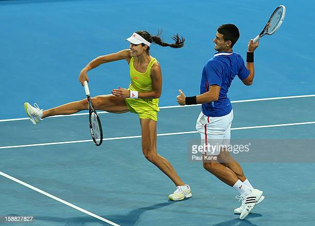 Ana Ivanovic and Novak Djokovic of Serbia volley in the mixed doubles match against against Francesca Schiavone and Andreas Seppi of Italy during day...