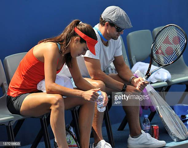 Ana Ivanovic of Serbia sits with Australian golfer and boyfriend Adam Scott as she takes a break during in a training session ahead of the 2012...