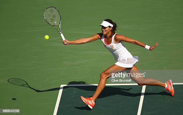 Ana Ivanovic of Serbia stretches to play a forehand against Carla Suarez Navarro of Spain in their first round match on Day 1 of the Rio 2016 Olympic...
