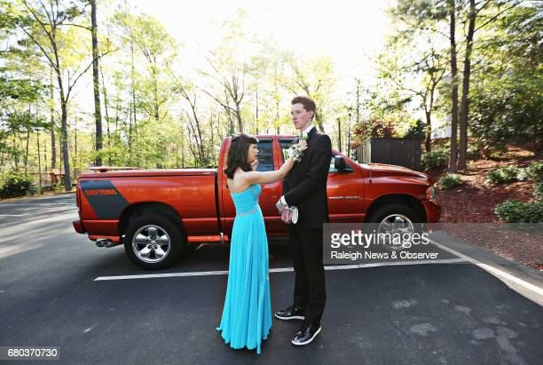 Ana Johnson left straightens the boutonniere of her prom date Jacob Hodgins right as she talks to her mom on the phone before the couple walk into...