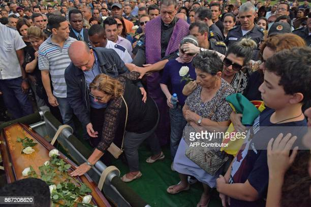 Ana Lucia Teixeira mother of deceased police colonel Luis Gustavo Teixeira lays flowers on his coffin during his funeral in Sulacap in western Rio de...