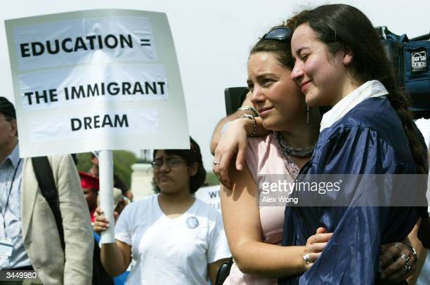 Ana Maria Archila and Carly Fox of the New York State Dream Act Task Force hold each other during a mock graduation ceremony at the West Front of the...