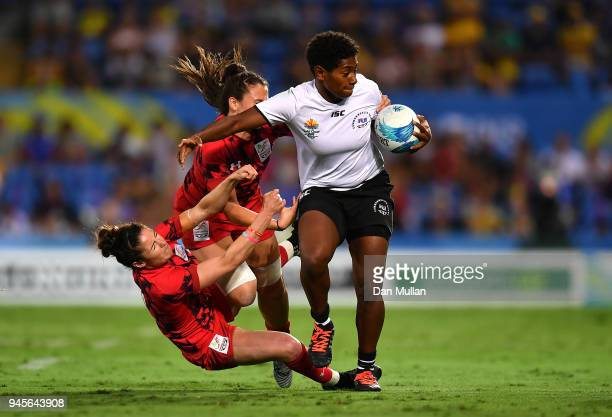 Ana Naimasi of Fiji is tackled by Sinead Breeze and Kayleigh Powell of Wales during the Rugby Sevens Women's Pool B match between Fiji and Wales on...