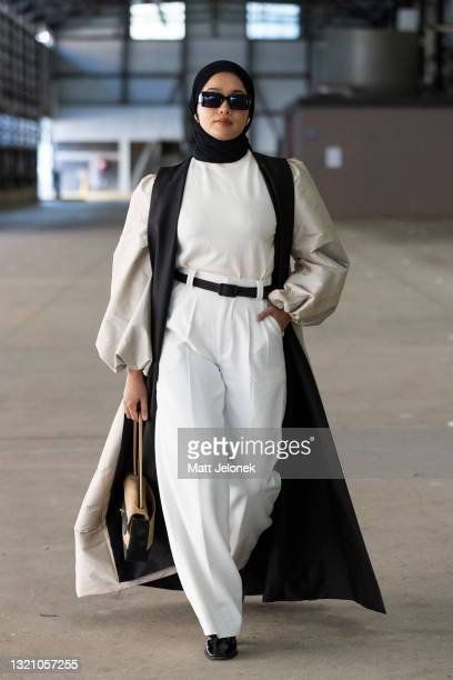 Ana Octarina is seen wearing an outer jacket by Anjilla Sadeqi, Dian Pelangi Studio scarf, Uniqlo top, a Day and Night Official pant with a vintage...