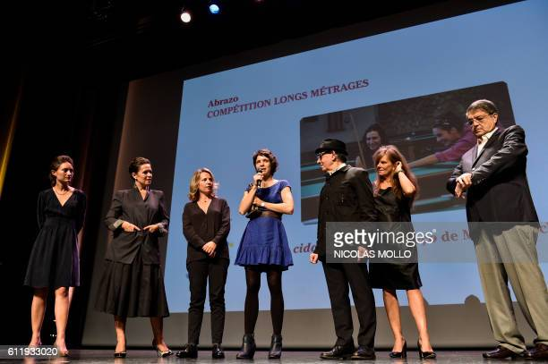 Ana Siqueira assistant director of the film A Cidade onde Envelheco speaks on stage after winning the 'Abrazo du meilleur film' award flanked by jury...