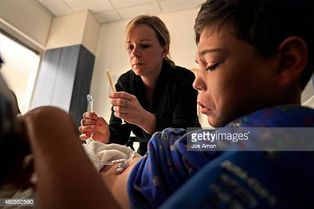 Ana Watson gives Preston Raynor his cannabidiol oil in the recovery room after getting his permanent feeding button in place at Children's Hospital...