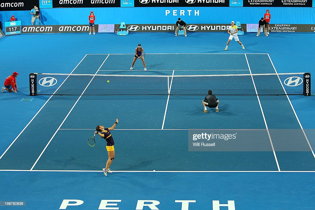 Anabel Medina Garrigues of Spain serves as Fernando Verdasco looks on in their mixed doubles match against Kevin Anderson and Chanelle Scheepers of South Africa during day one of the Hopman Cup at Perth Arena on December 29, 2012 in Perth, Australia.