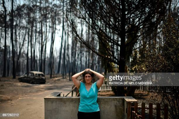TOPSHOT Anabela Silva stands in front of her house with her burnt car in the background after a wildfire in Figueiro dos Vinhos on June 18 2017 A...