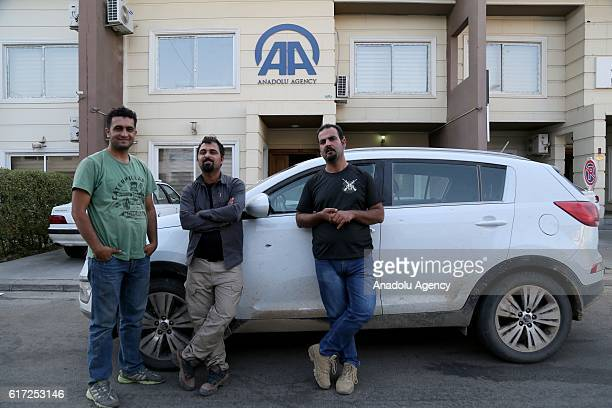 Anadolu Agency photojournalists Hemn Baban Yunus Keles and cameraman Ihsan Muhammed pose in front of their damaged car in Erbil Iraq on October 22...