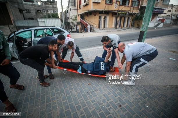 Anadolu Agency's cameraman Mohammad al-Aloul is being carried with a stretcher to hospital after he and photojournalist Mustafa Hassouna were injured...