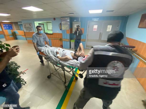Anadolu Agency's cameraman Mohammad al-Aloul is being carried with a stretcher to be transferred for his treatment Al-Quds Hospital following an...