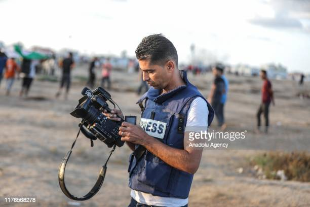 Anadolu Agency's photojournalist Muhammed Dahlan holds his damaged camera after it was shot with a rubber bullet by Israeli soldiers during protests...