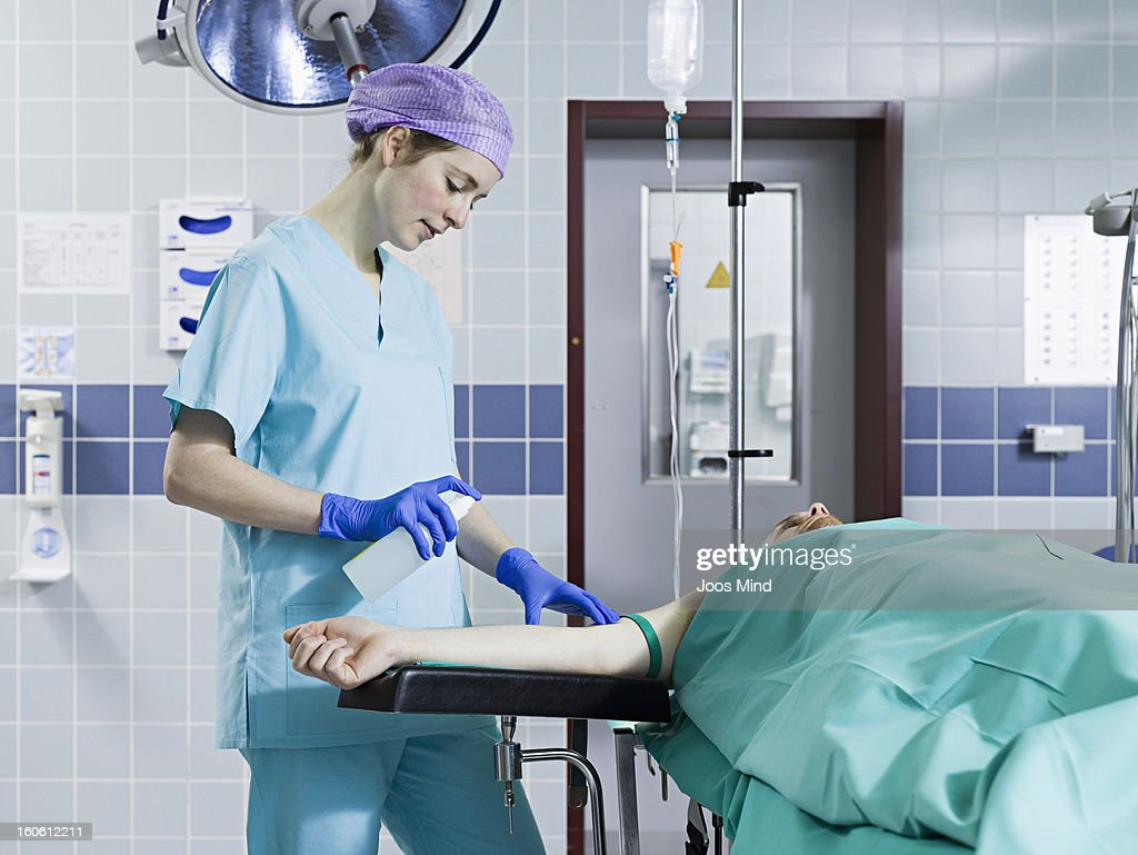 anaesthetist sanitizing patients arm : Stock Photo