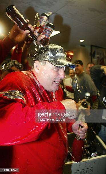 Anaheim Angels' manager Mike Scioscia is doused with beer as he prepares to spray his players with champagne in the Angels' locker room as the team...