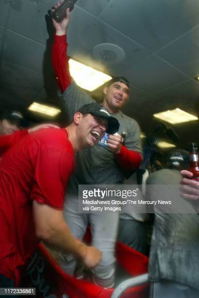 Anaheim Angels right fielder Tim Salmon stands in the champagne bucket in the Angels locker room after they defeated the San Francisco Giants in game...