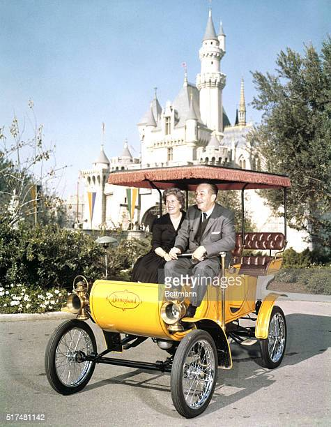 Anaheim Ca Walt Disney sits with wife in an antique auto at Disneyland