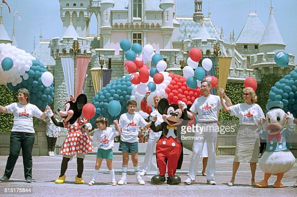 Minnie Mouse Mickey Mouse and the president of Walt Disney Productions Frank G Wells stand in the 'Hands Across America' line in front of Sleeping...
