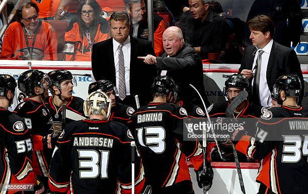Anaheim Ducks assistant coach Bob Woods along with head coach Bruce Boudreau and assistant coach Brad Lauer congratulate the team on their victory...