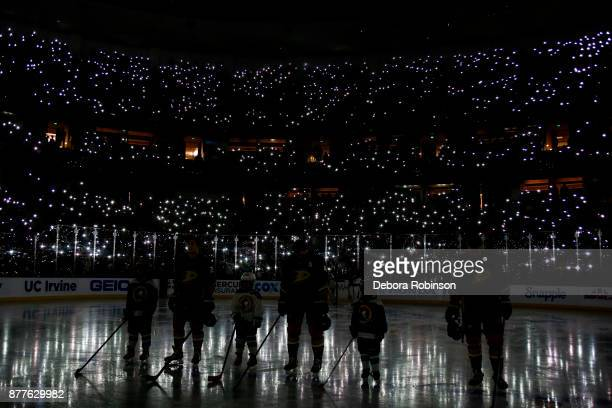 Anaheim Ducks bow their heads as fans turn on their cell phone flashlights during a moment of silence for Hockey Fights Cancer before the game...
