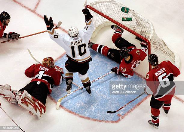 Anaheim Ducks Corey Perry celebrates Andy McDonald's first goal of two past Ottawa Senators goaltender Ray Emery left on his stomach Andrej Meszaros...