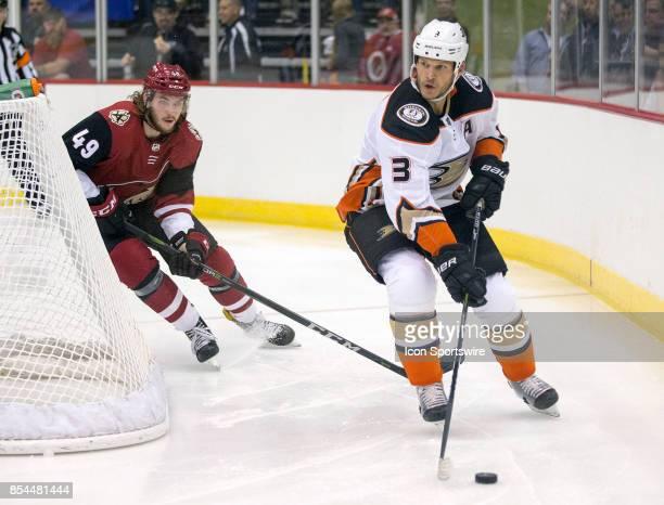 Anaheim Ducks defenseman Kevin Bieksa controls the puck while Arizona Coyotes center Ryan MacInnis tracks him down during a preseason hockey game...