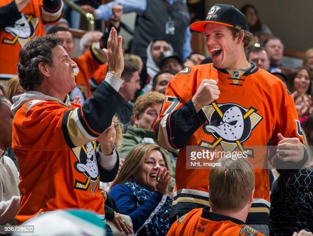 Anaheim Ducks fans celebrate after catching a puck in the stands during the third period of the game against the New Jersey Devils at Honda Center on...