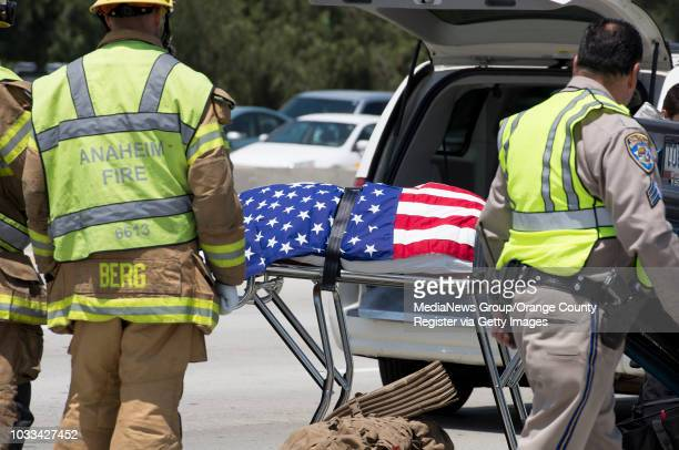 Anaheim Firefighters and California Highway patrol assist as a American flag was draped over the body of a Marine who was killed Wednesday morning in...