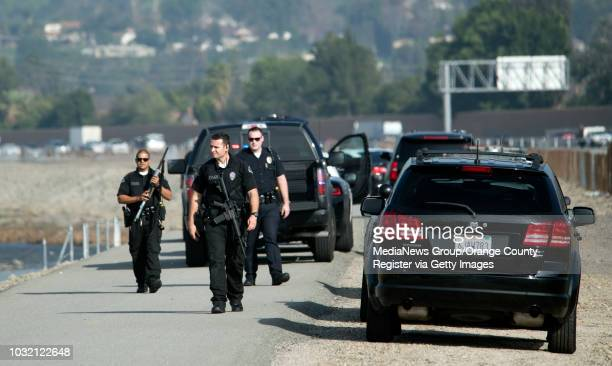 Anaheim police officers search for a man car thief suspect after he rammed an undercover officer then escaped by running across the Santa Ana river...