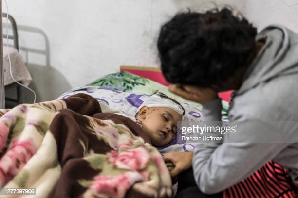 Anahit Gevorgyan sits with her son Artsvik after he was injured and her eight-year-old daughter was killed by fighting in their village of Martuni...