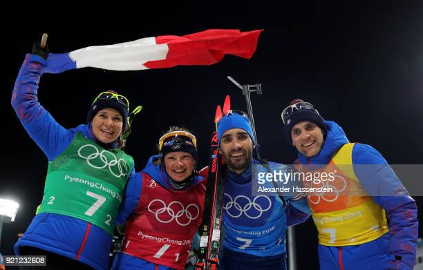 Anais Bescond Marie Dorin Habert Martin Fourcade and Simon Desthieux of France celebrate after winning the gold medal during the Biathlon 2x6km Women...
