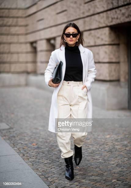 Anais Eleni is seen wearing white wool coat Sandro black turtleneck Luisa Cerano creme white jeans Ksenia Schnaider black Massimo Dutti leather...