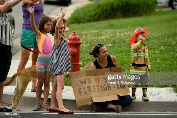 Analee Gilpin in shorts her twin sister Tava both 9 Laura Wegner seated and her son Silas wave at firefighters during shift change as they come on...
