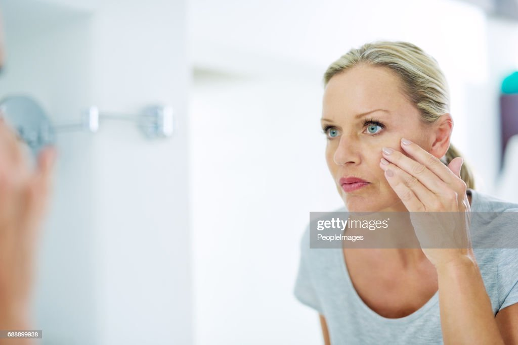 Analysing her skin for any blemishes : Stock Photo
