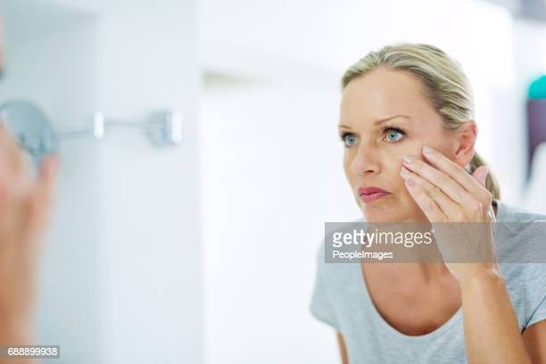 analysing her skin for any blemishes - woman in mirror stock photos and pictures