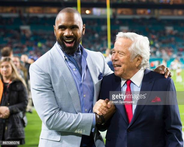 Analyst Charles Woodson and New England Patriots owner Robert Kraft smile and shake hands on the field before the start of the NFL football game...