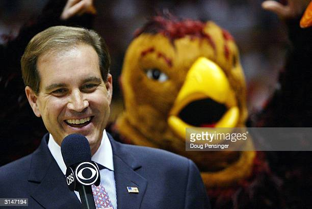 CBS analyst Jim Nantz shows a smile as the St Joseph's Hawks mascot flaps his arms in the background before the start of the fourth round regional...