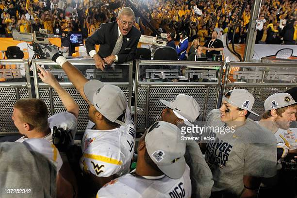 Analyst Lou Holtz congratulates players from the West Virginia Mountaineers after they won 70-33 against the Clemson Tigers during the Discover...