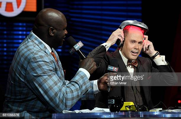 NBA analyst Shaquille O'Neal looks on as TNT's Inside the NBA host Ernie Johnson Jr puts on an iGrow laserbased hairgrowth helmet during a live...