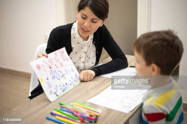 analyzing his drawings - autism spectrum disorder stock photos and pictures
