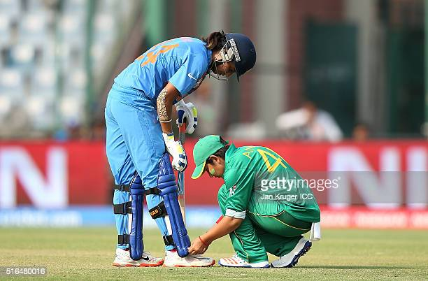 Anam Amin of Pakistan helps Harmanpreet Kaur of India tie a shoe lace during the Women's ICC World Twenty20 India 2016 match between India and...