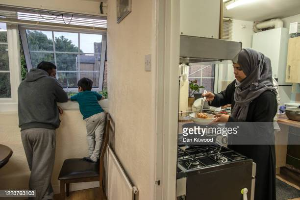 Anam prepares food for iftar while Daniel and his uncle Rizwan look at a fox from their first floor window at their family home on May 08 2020 in...