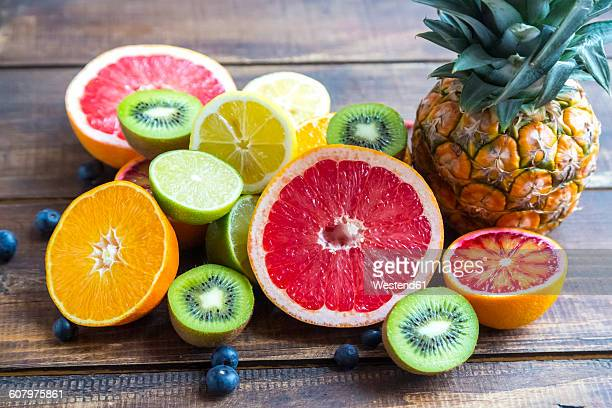Ananas, blueberries, wolfberries, kiwis and sliced citrus fruits on wood