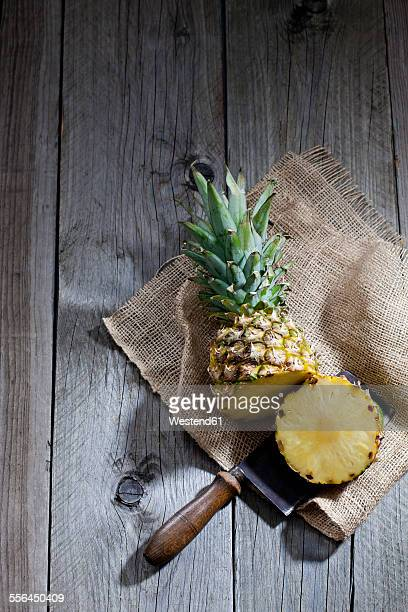 Ananas, jute and old cleaver on wood
