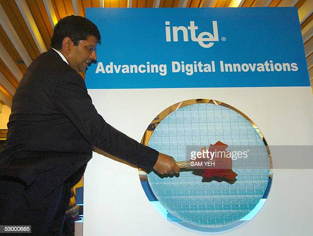"""Anand Chandrasekher, Vice President of Intel Corporation, knocks a wafer shaped gong to mark the """"daul core"""" motherboard during the Computex Taipei..."""