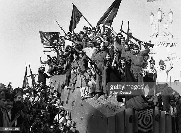 Anarchist militia from the National Confederation of Labour wave their flags and rifles for the camera in Barcelona during the Spanish Civil War |...