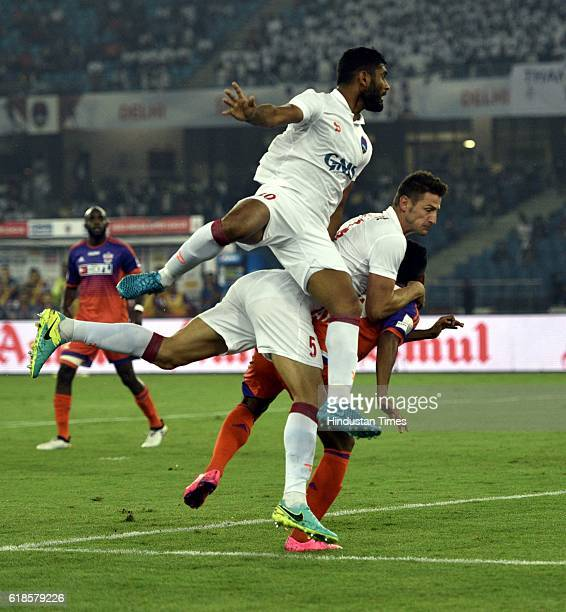 Anas Edathodika and Ruben Gonzalez of Delhi Dynamos FC shuffle with players of FC Pune City during the India Super League football match on October...
